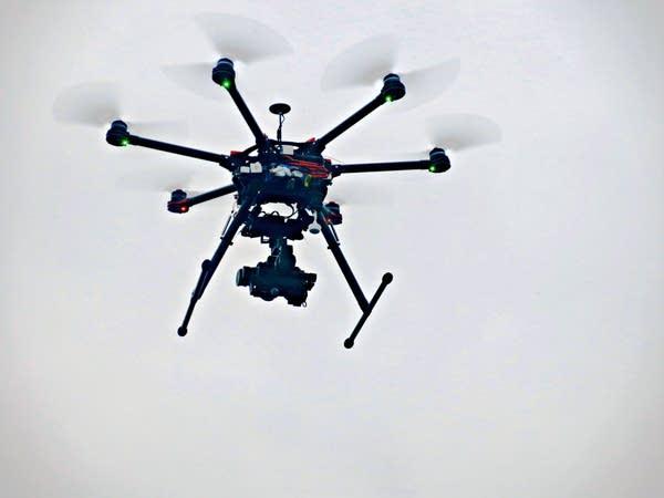 A drone rises into a gray sky.