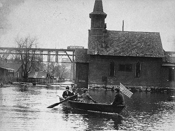 Boys rowing boat down street in Bohemian Flats