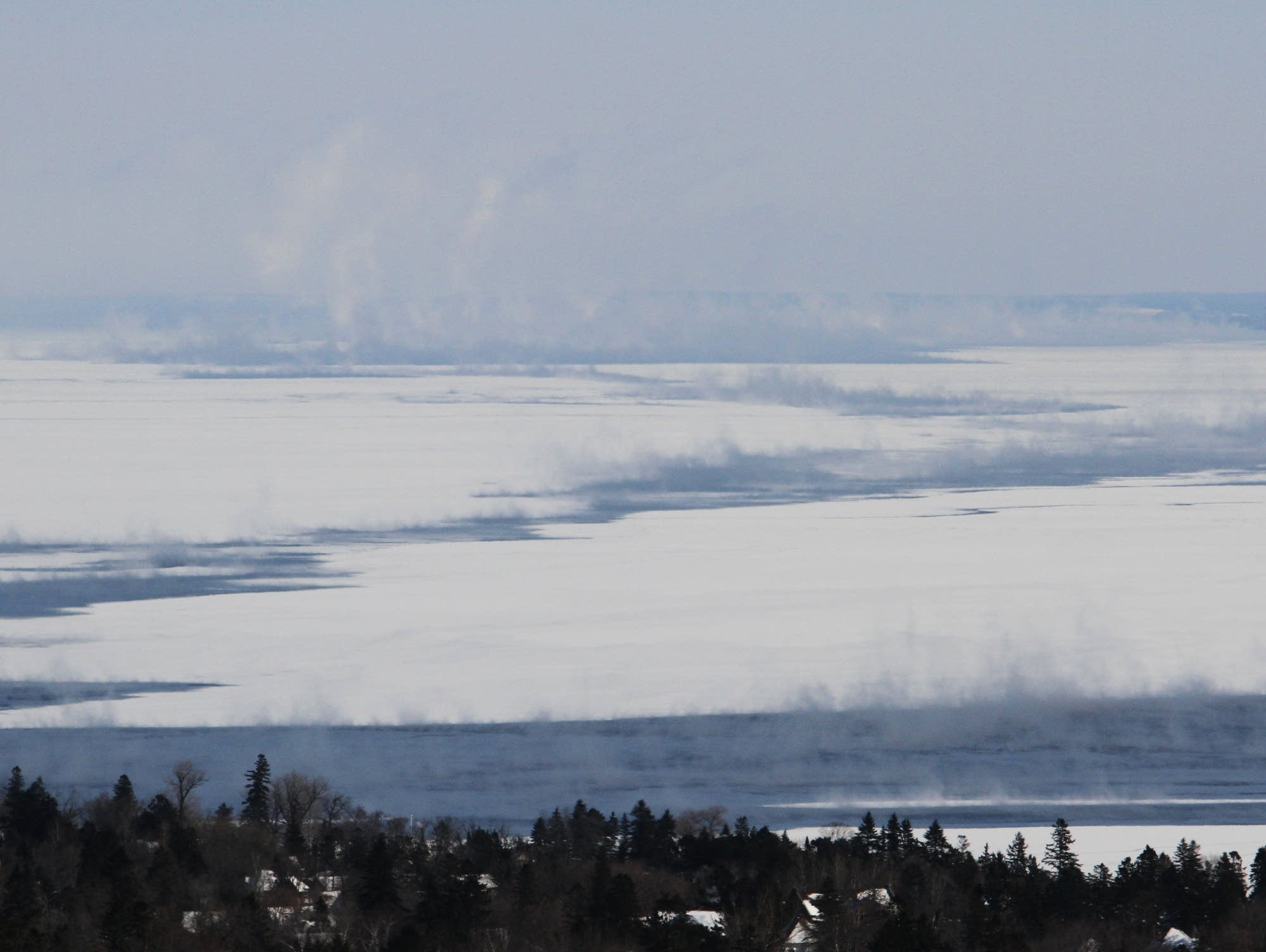Sea smoke rises from patches of open water on icy Lake Superior