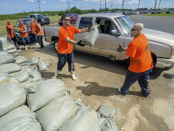 St. Bernard Parish Sheriff's Office inmate workers move free sandbags.