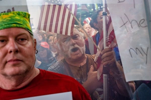 A man with a mustache and a hand over his heart holding a flag behind glass