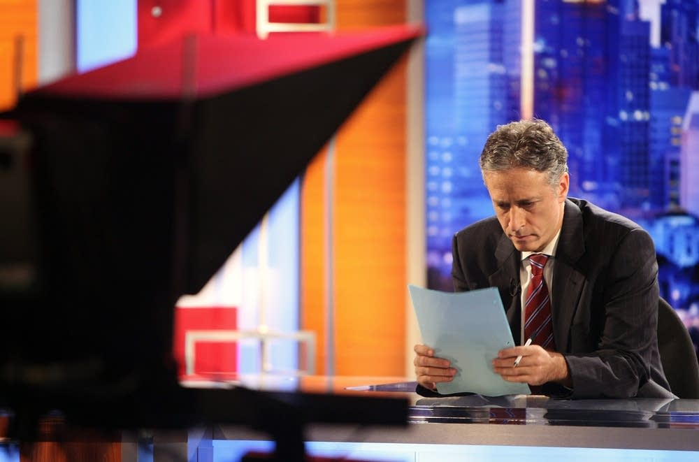 Jon Stewart reads notes during a break