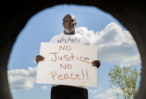 """A man holding a sign that reads """"No justice, no peace!!"""""""