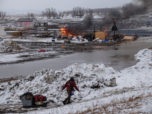 A campsite burns as protesters leave the Oceti Sakowin camp