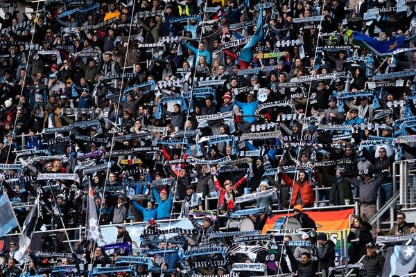 Minnesota United fans hold their scarves up while cheering for the team.