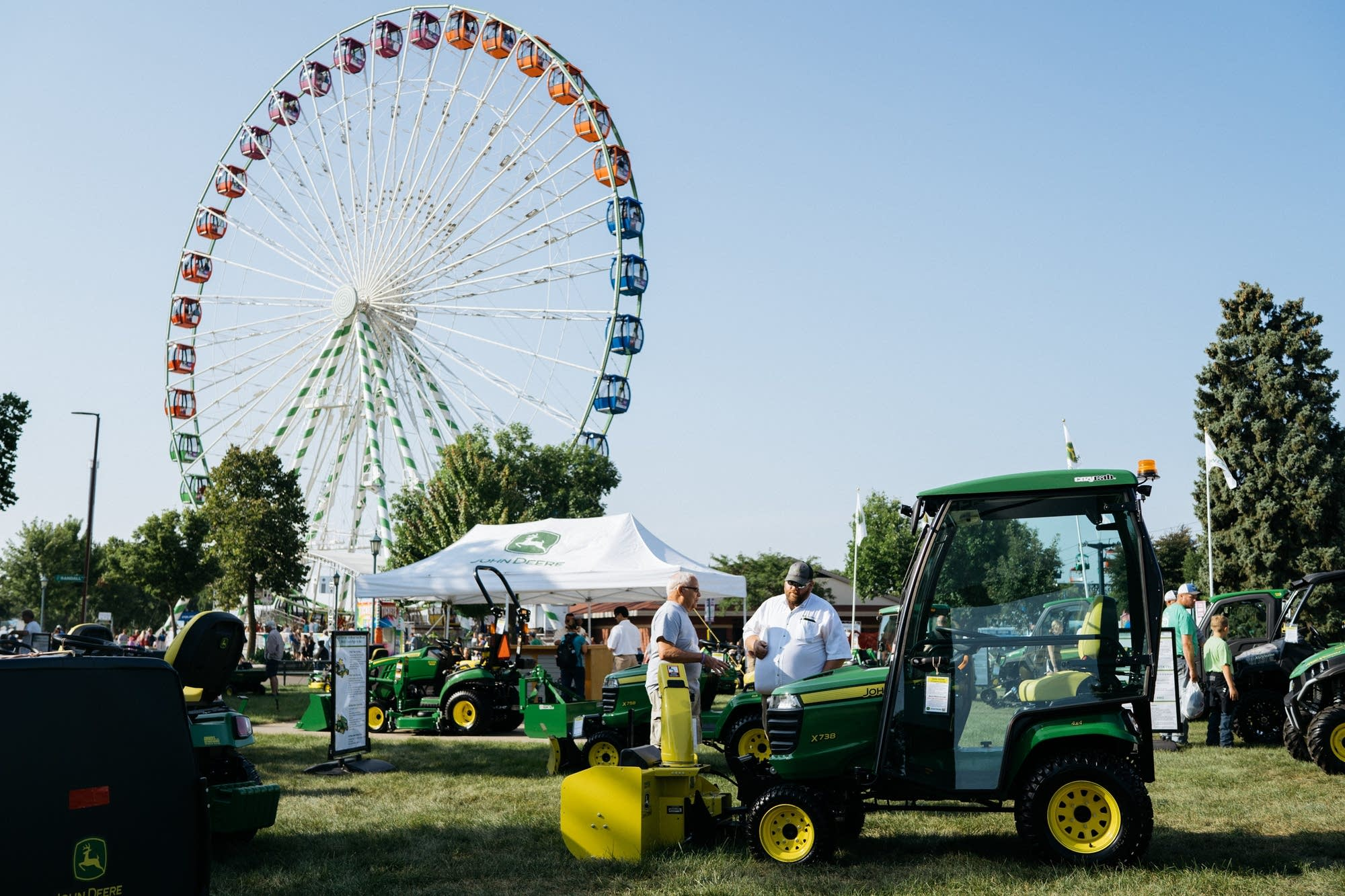 A ferris wheel turns as people check out John Deere tractors.