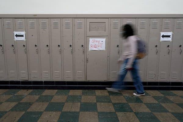 A student walks down a hallway.