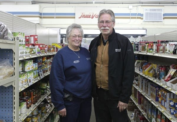 Two people stand between two shelves filled with food.