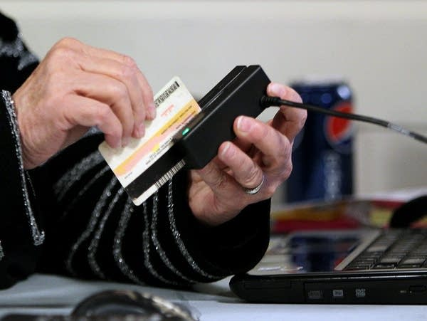 A man swipes an ID Card through an electronic reader.