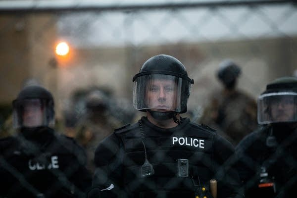 A man in riot gear looks through a fence.