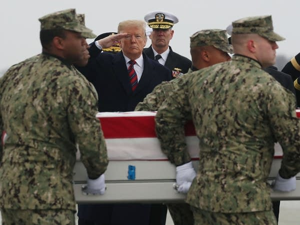 President Trump salutes as a military team moves a casket