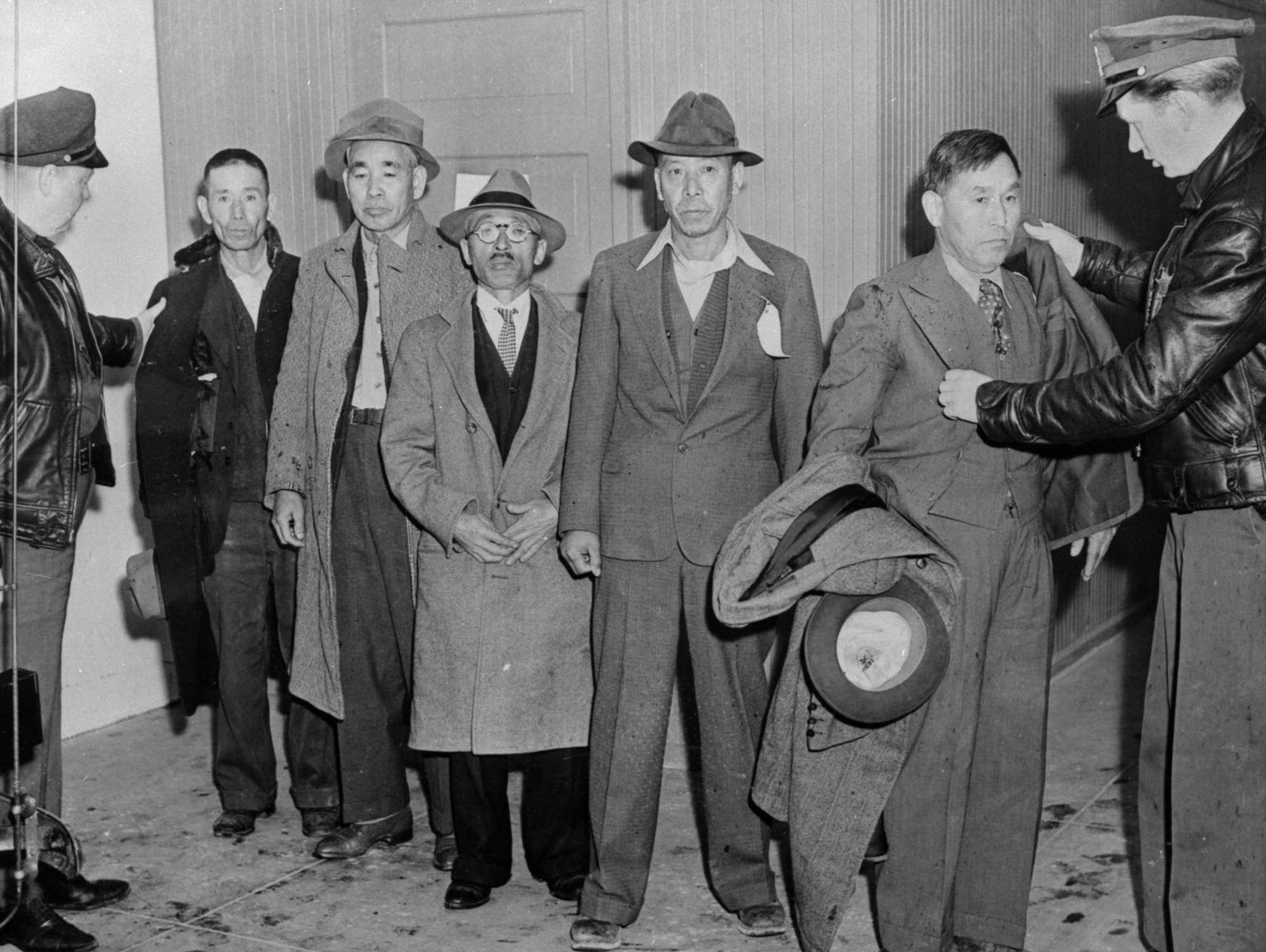 Law enforcement officers search Japanese aliens during WWII.