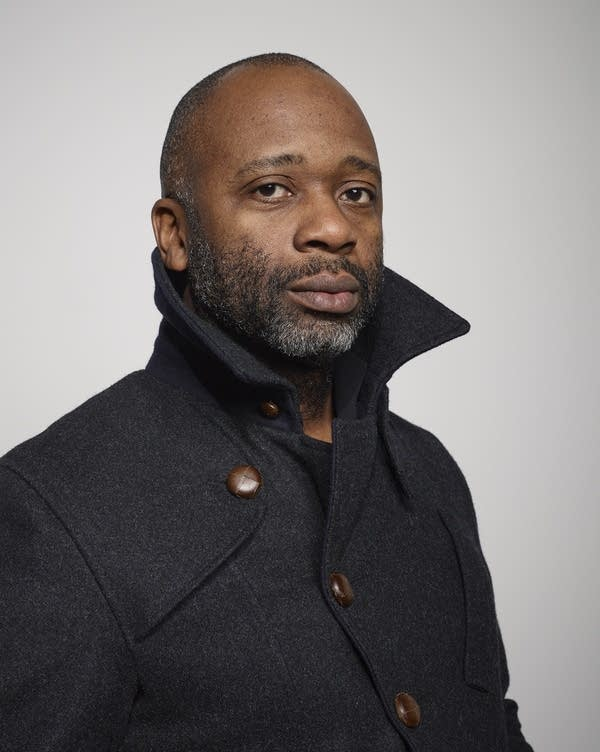 A man wears a gray wool coat.