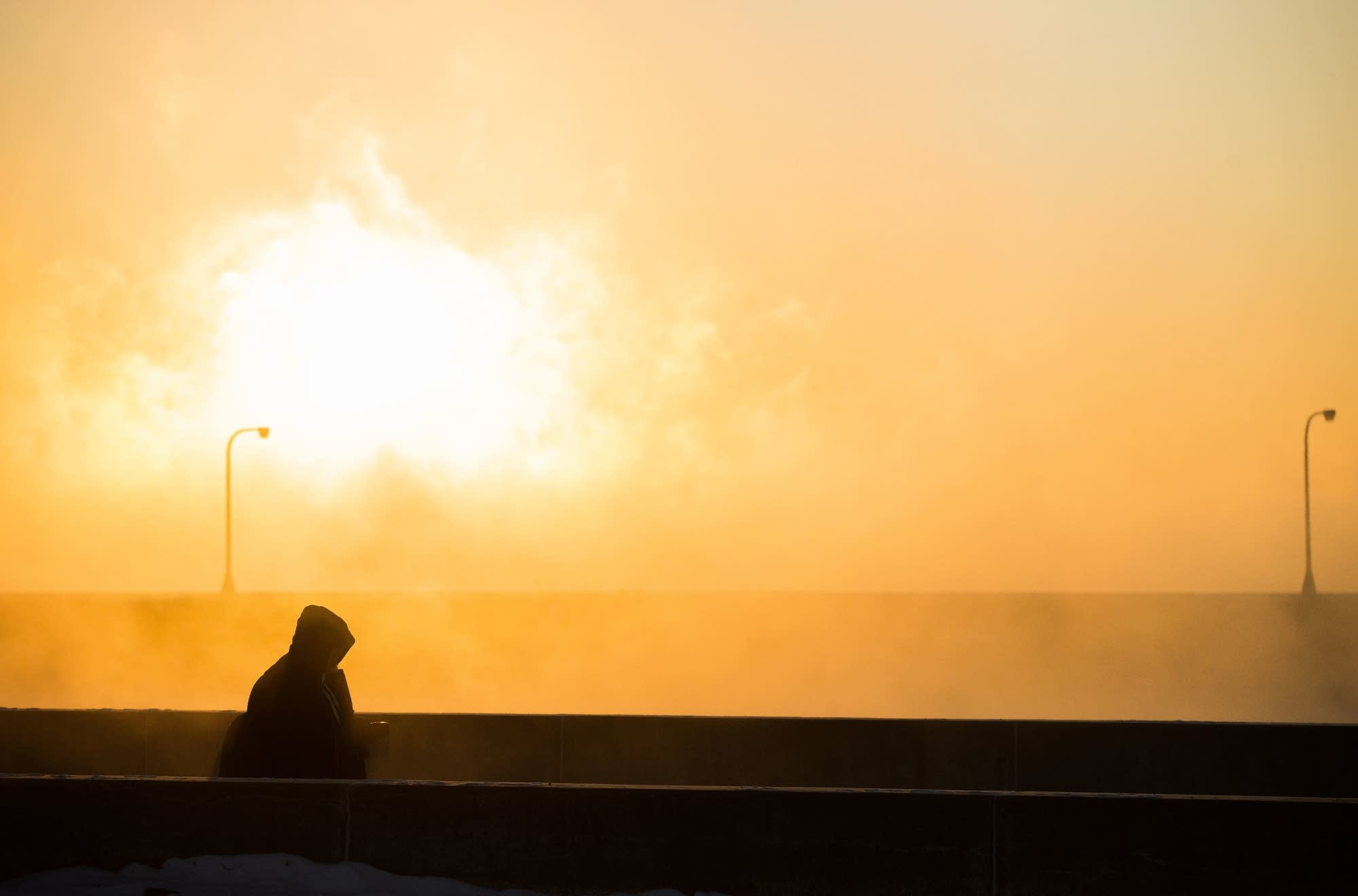 A photographer is silhouetted by the rising sun and sea smoke.