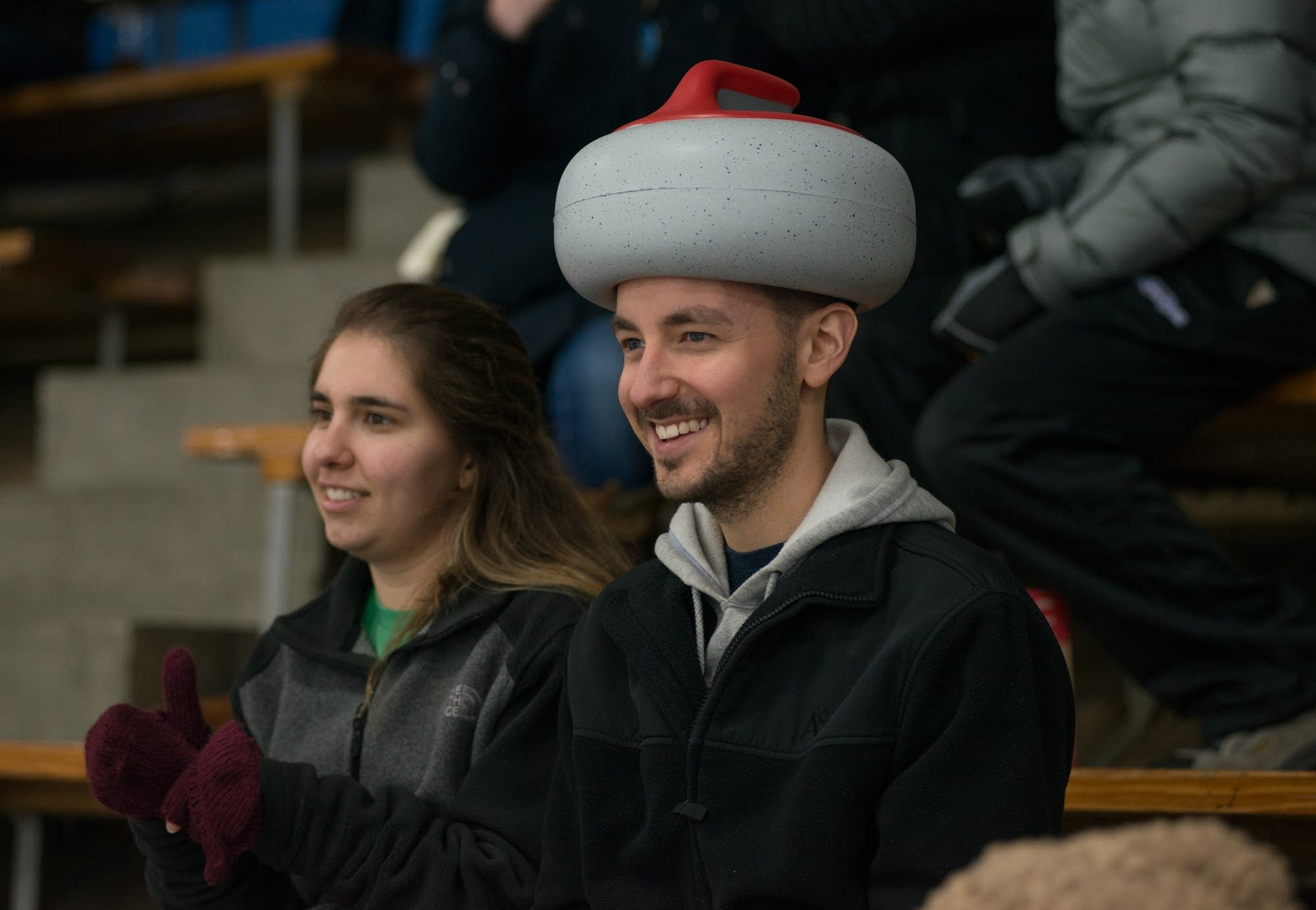Matthew Ammon watches the finals  in his curling stone hat.