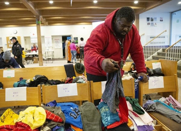 A man holds looks through clothes piled on chairs.