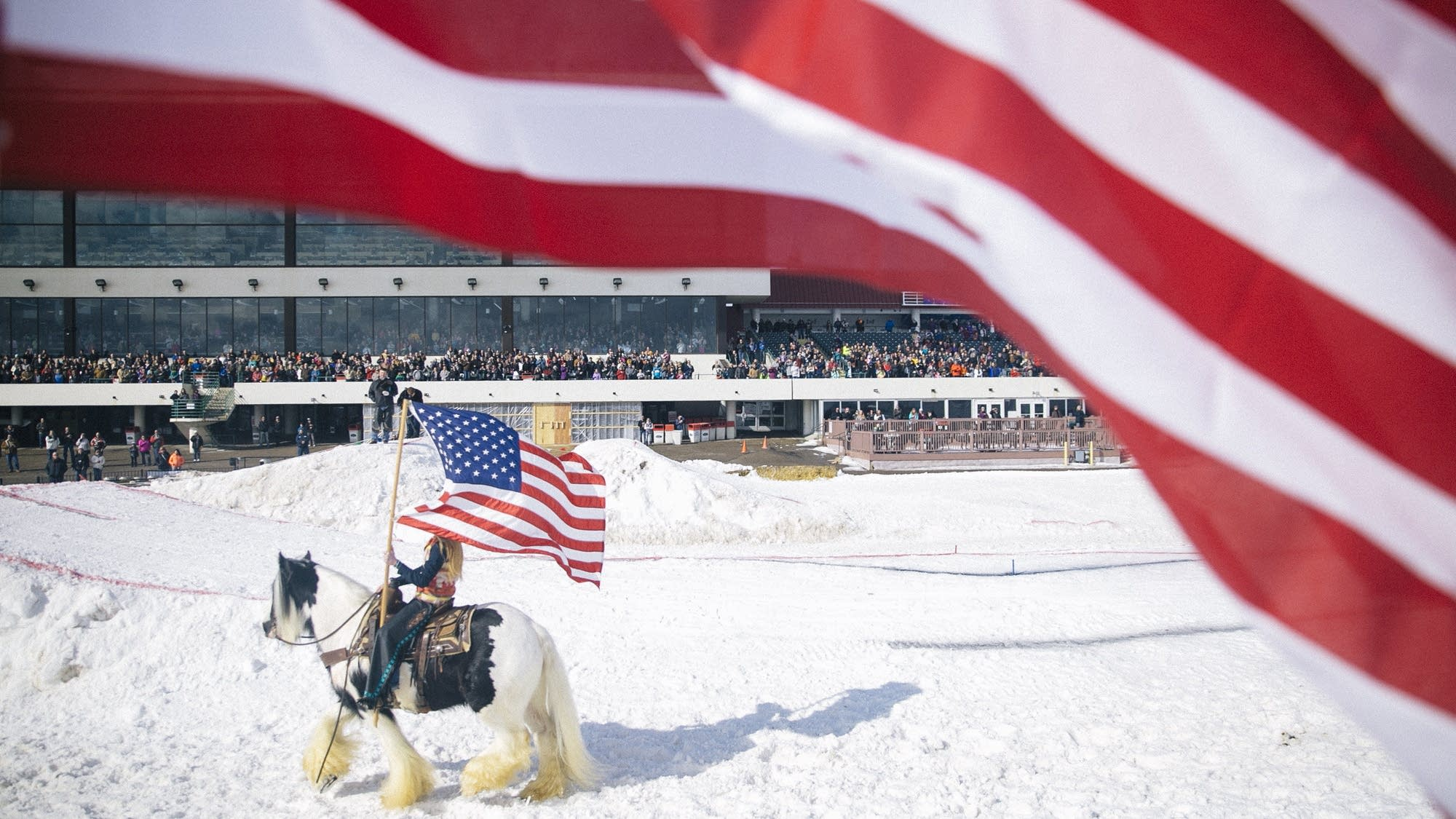 A  horse named Dirty Harry carries a rider and flag during the anthem.