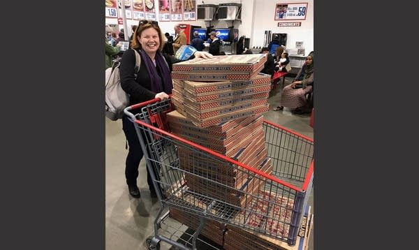 White 40ish Woman (Genevieve) pushing grocery cart full of 30 large pizzas