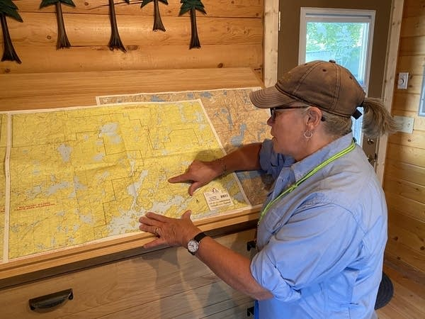 A person points to an area on a large map.