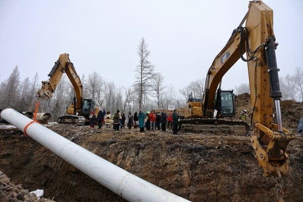A pipe is lowered into a ditch.