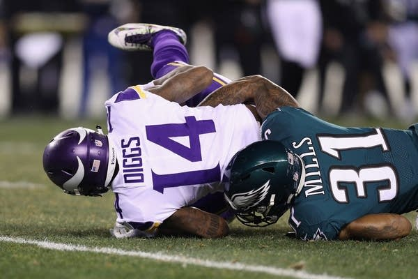 Stefon Diggs (14) of the Minnesota Vikings is tackled by Jalen Mills (31).