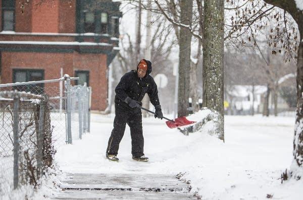 Jim Gates shovels his and his neighbor's sidewalk.