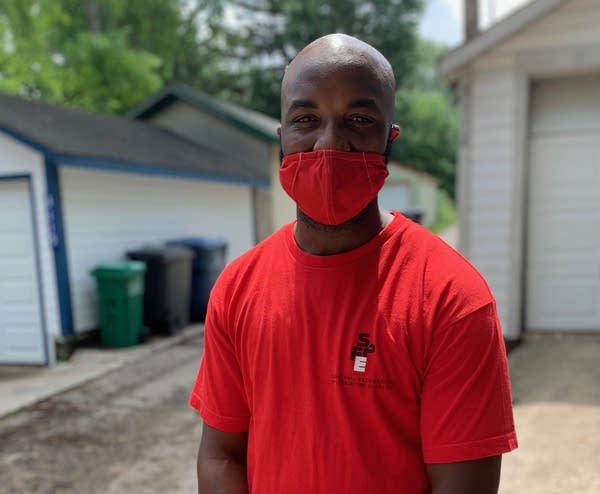 A man wears a red face mask and red t-shirt.
