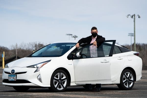 A man stands next to his white prius.