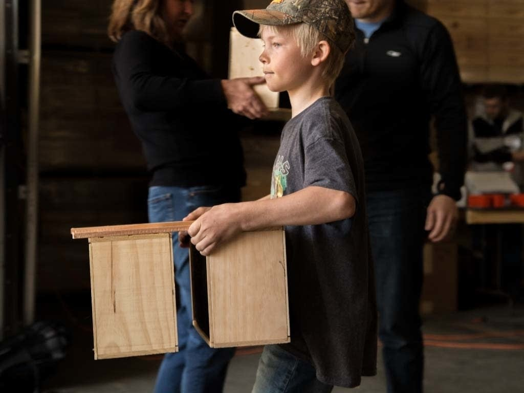 Jesse Koskiniemi concentrates as he carries two crates full of bees.