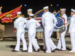 A United States Navy honor guard carries the remains of Dante Tini