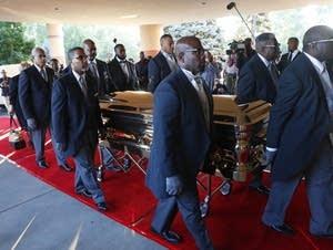 Pallbearers carry the gold casket of legendary singer Aretha Franklin.