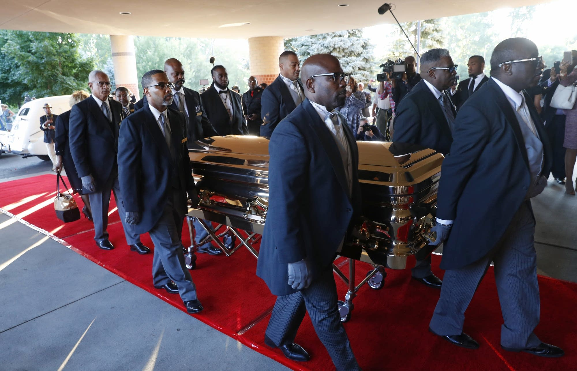 Pallbearers carry the gold casket of legendary singer Aretha Franklin.