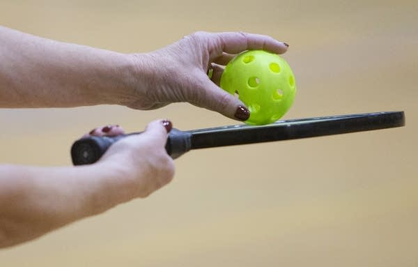A close up of a hands holding a green ball and a paddle.