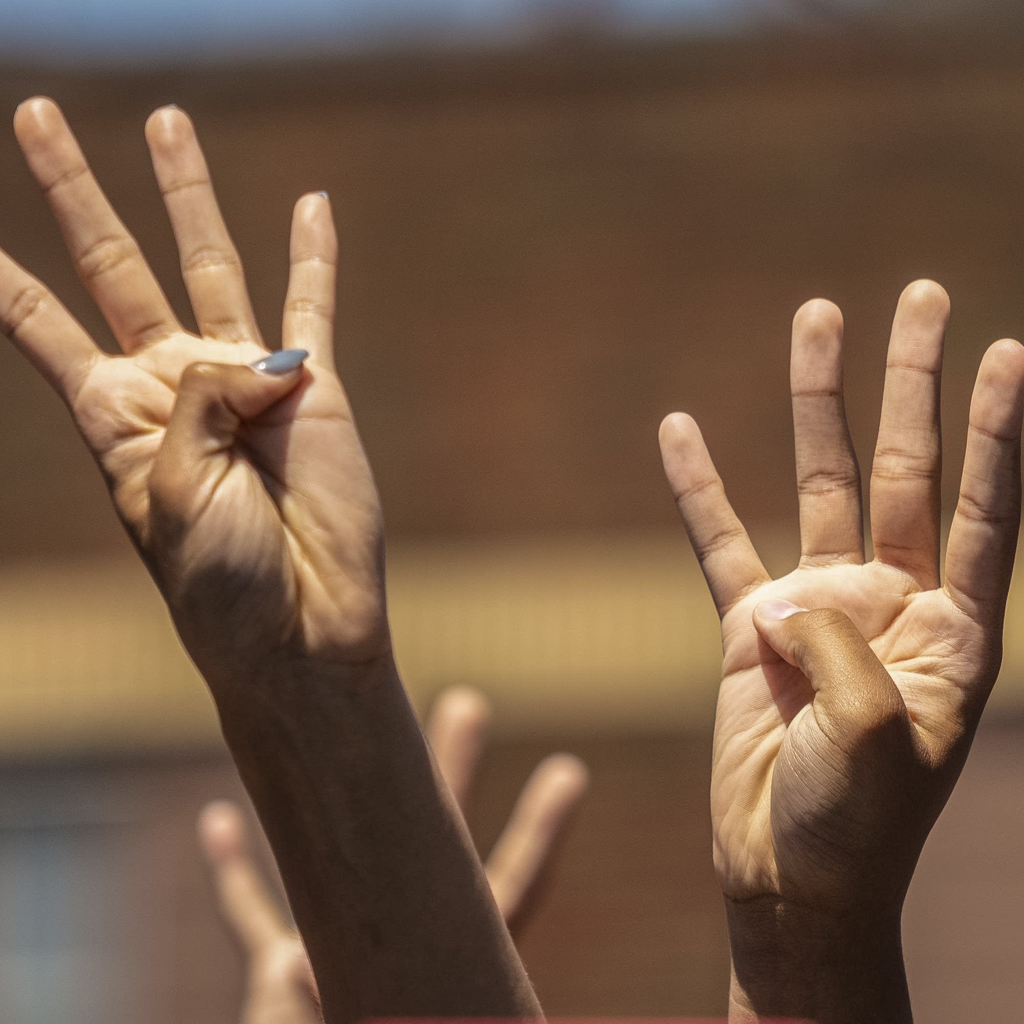 People hold up four fingers