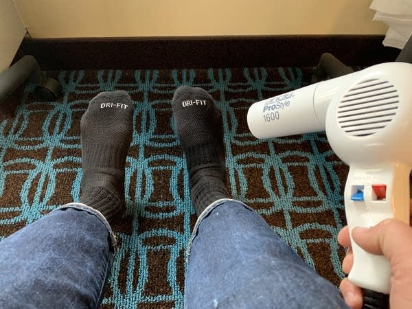 A pair of feet wearing black socks being warmed by a hair dryer