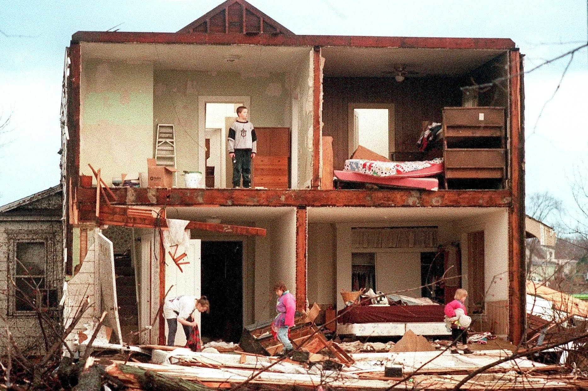 Family members search for the family cat shortly after a tornado.