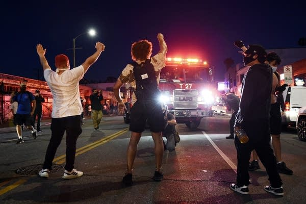 Demonstrators block the path of a Los Angeles Fire Department truck.