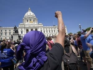 Person raising arm in front of a capitol building.