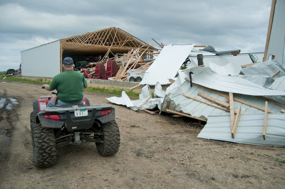 Robert Nienow drives past one of his damaged sheds