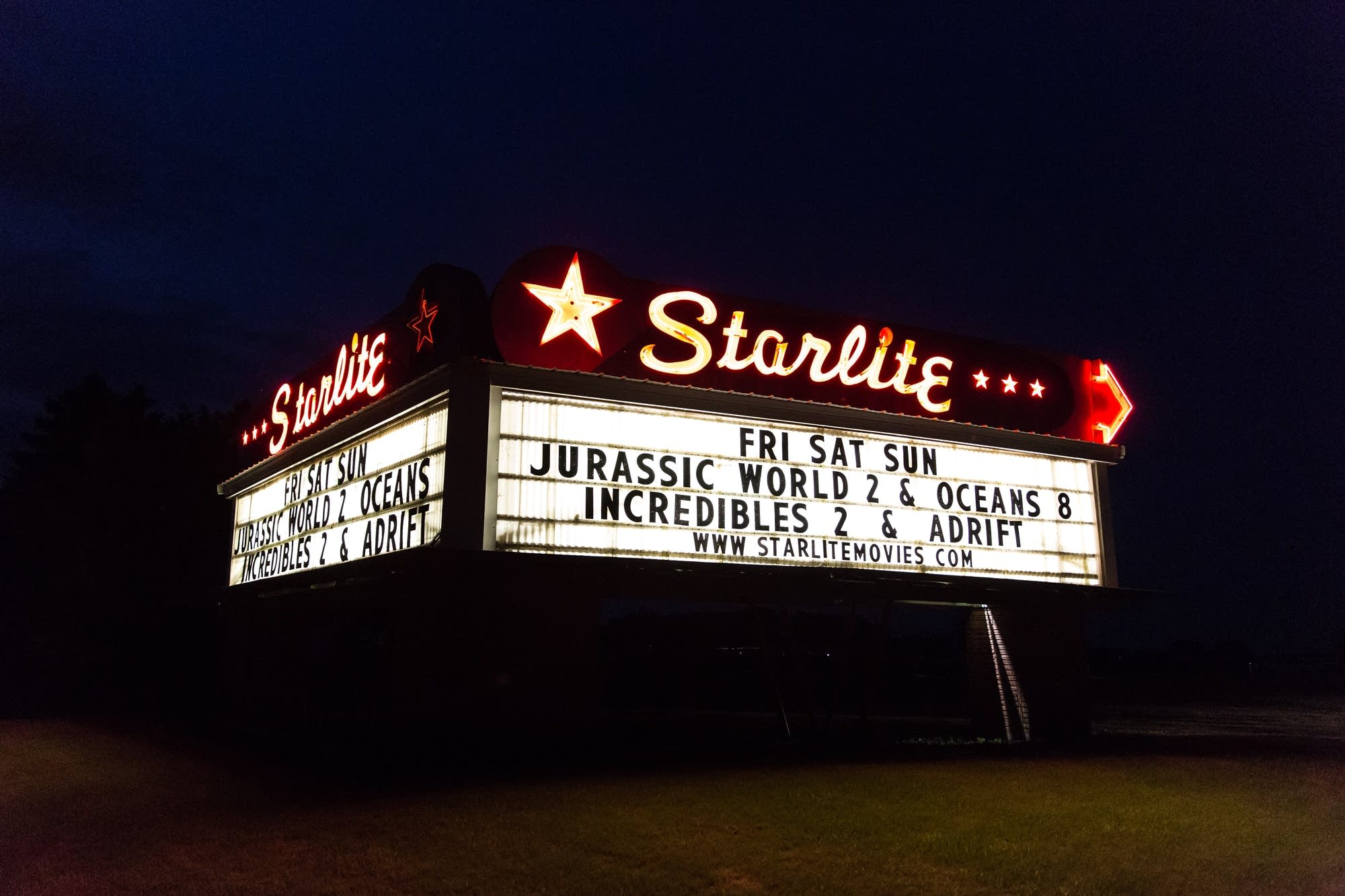 The Starlite Drive-In Theater's neon marquee sits alongside Highway 22.