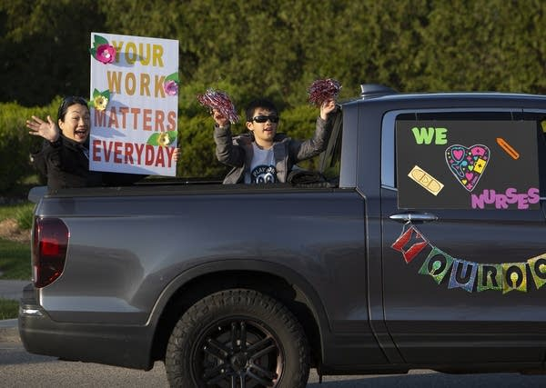 People wave and hold signs from the back of a truck.