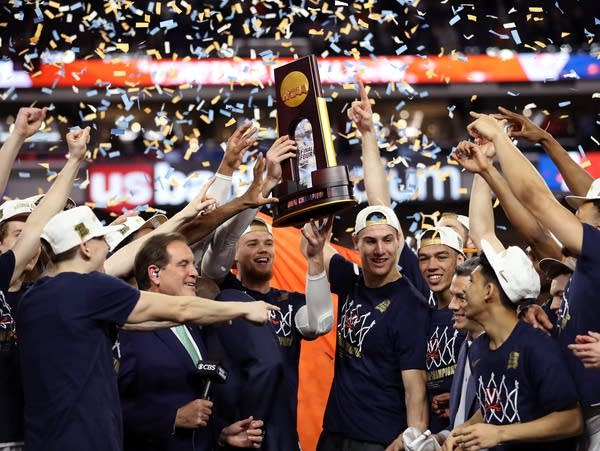 The Virginia Cavaliers celebrate with the trophy.
