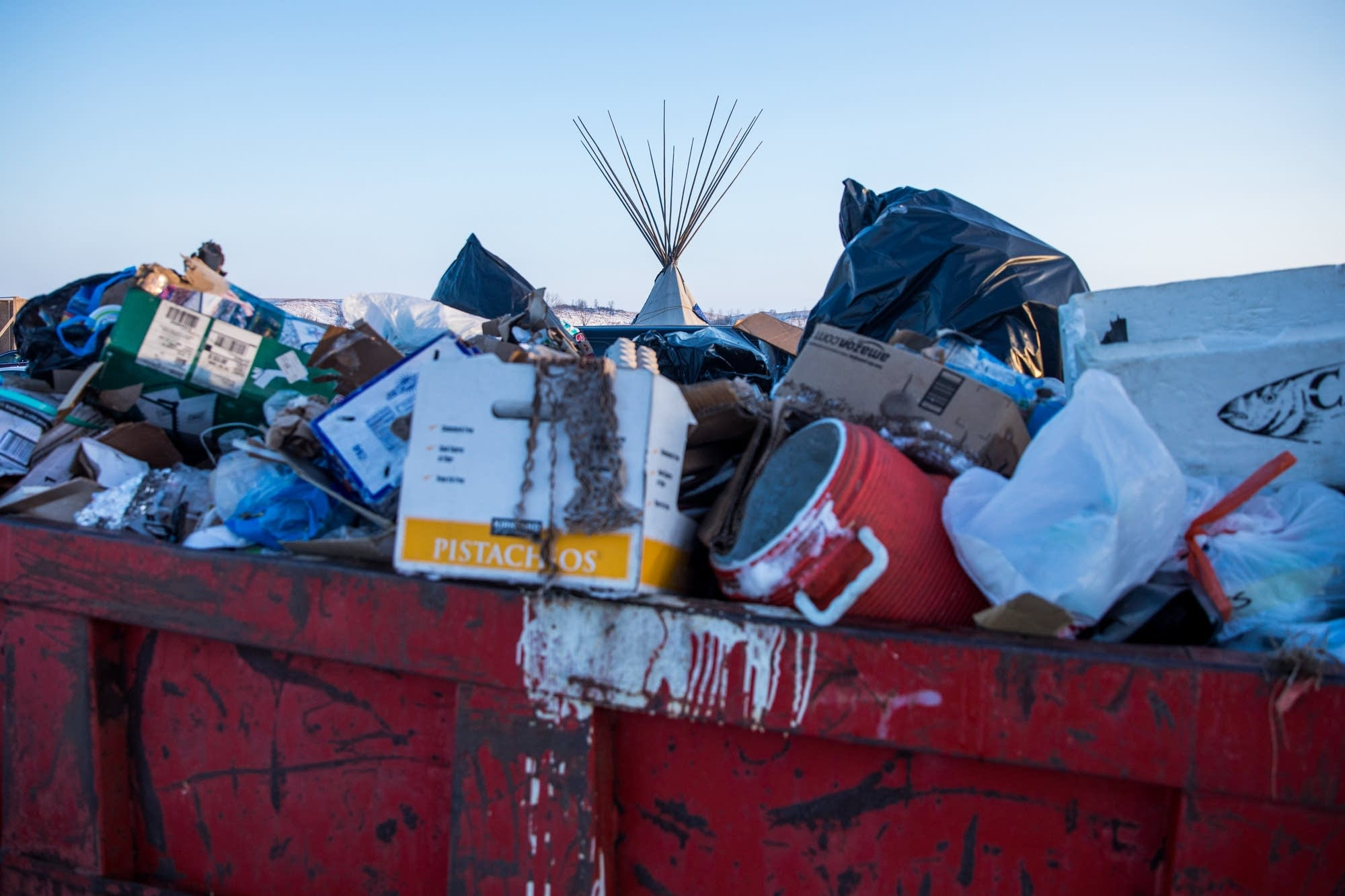 A teepee is seen from behind a dumpster.