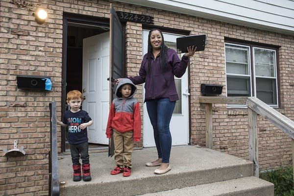 A woman standing on the stoop of a house with two children.