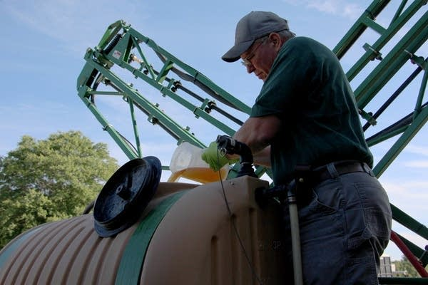 John Draper pours glyphosate into the tank of his sprayer.