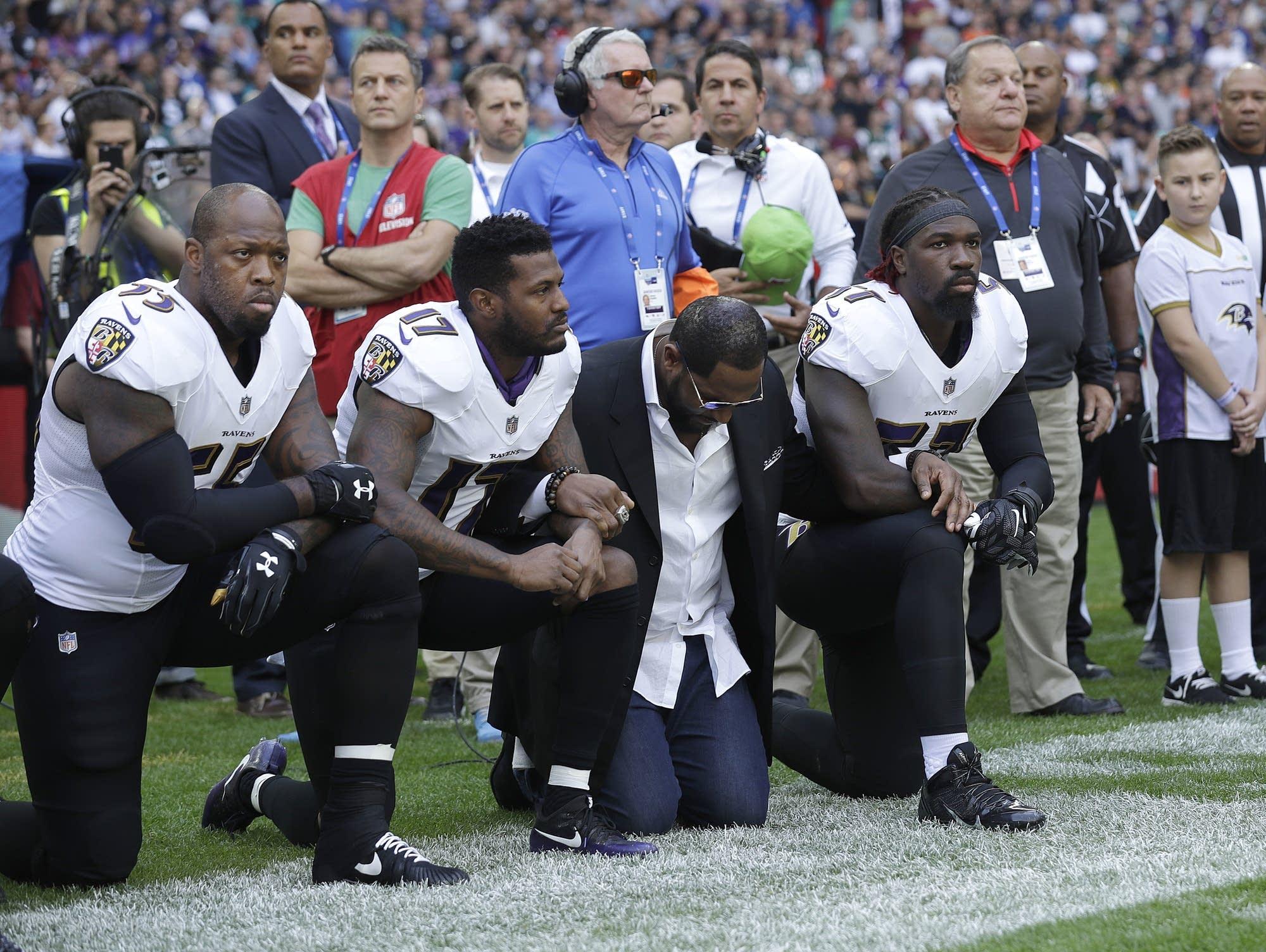 Baltimore Ravens players kneel down during anthem