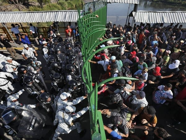 Migrants charge on the Mexican National Guardsmen