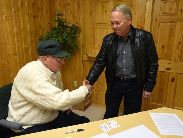 Larson extended a hand to Allen after a card draw reelected Allen mayor.