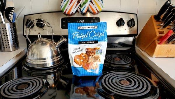 Blue bag of Pretzel Crisps sitting on stove, next to teapot