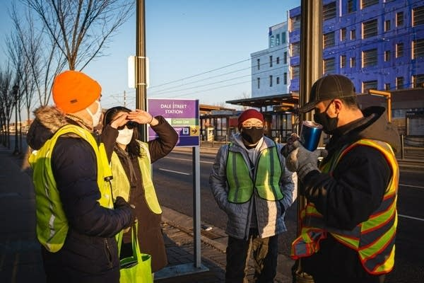 A group of people stand outside near by a light rail station.